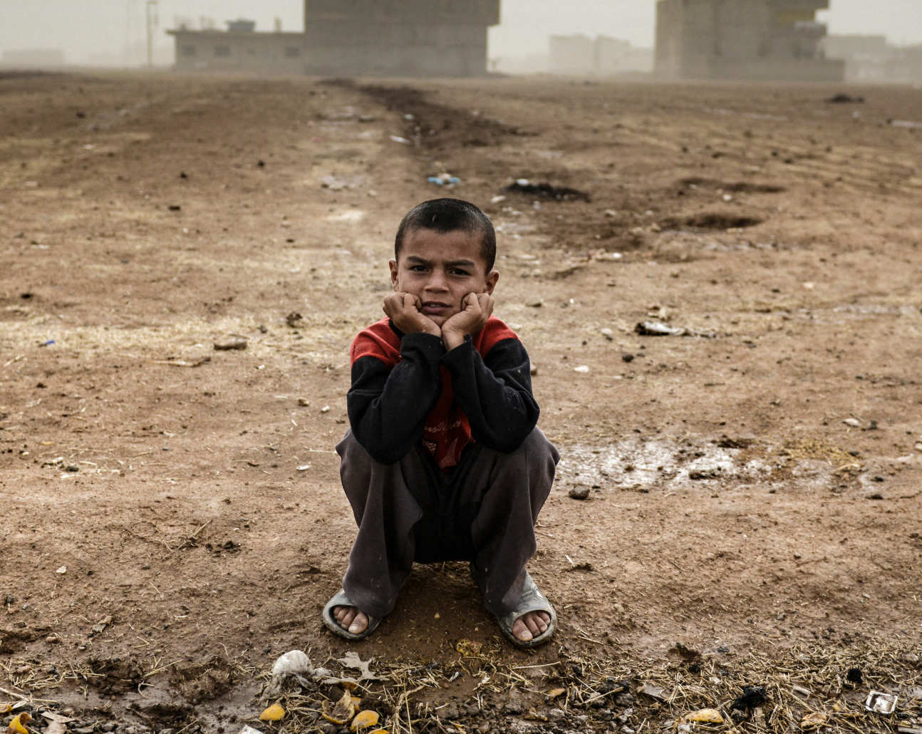 A young boy sitting in a mine field