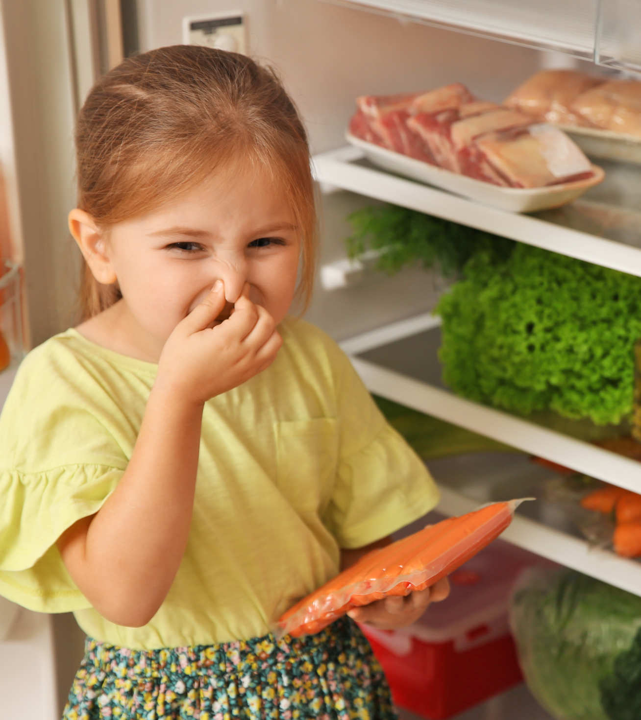 Photo of little girl next to open fridge holding a packet of sausages and pinching her nose