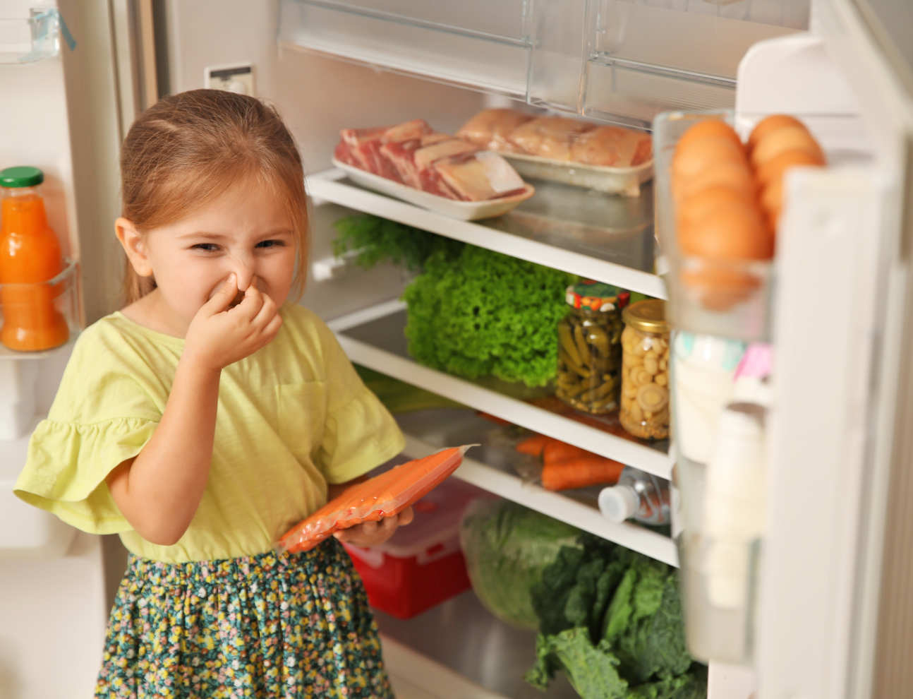 little girl holding nose next to a fridge to indicate that food inside has gone off