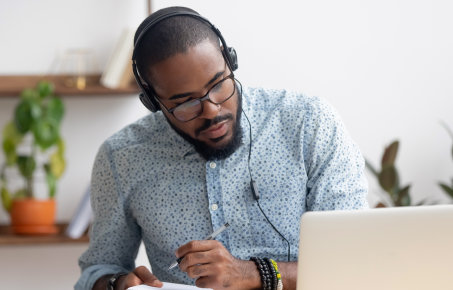 Man wearing headphones at a laptop
