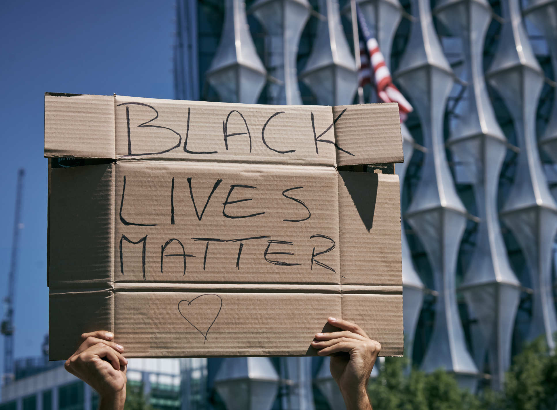 person holds up cardboard which says 'Black Lives Matter'