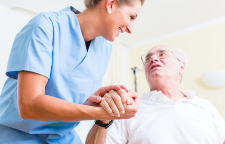 A female nurse holding the hand of an elderly man