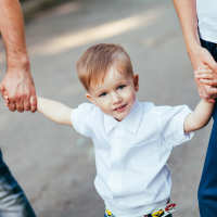 Parents holding child's hand