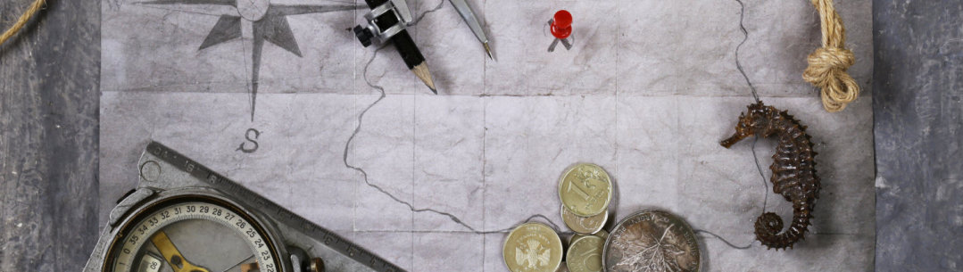 Photograph of map, compas and coins