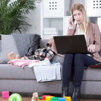 Woman on sofa with toys and laptop