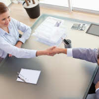 Man and woman shaking hands across desk