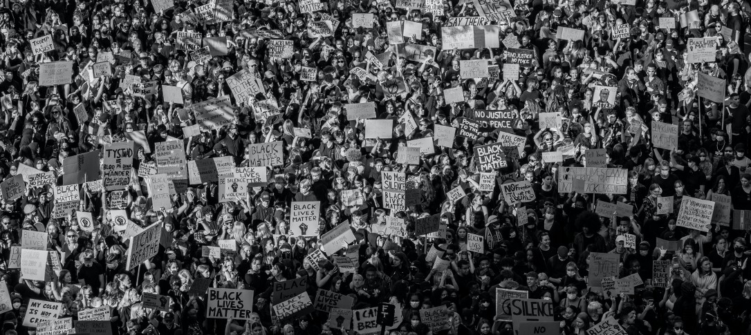 A black and white aerial image of a crowdof people, some with placards,  during a Black Lives Matter protest.