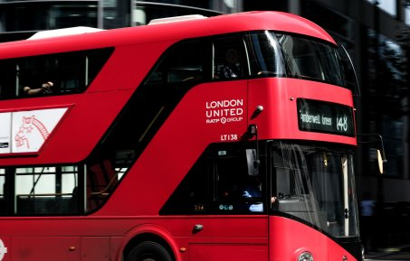 The iconic red london bus in motion