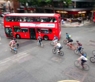 Red bus in London with lots of cyclists following