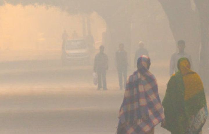 Two women walking along a road that is hazy with air pollution