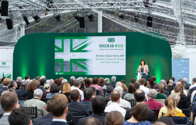 Claire Perry standing on a stage next to Green GB week branding with an audience in front