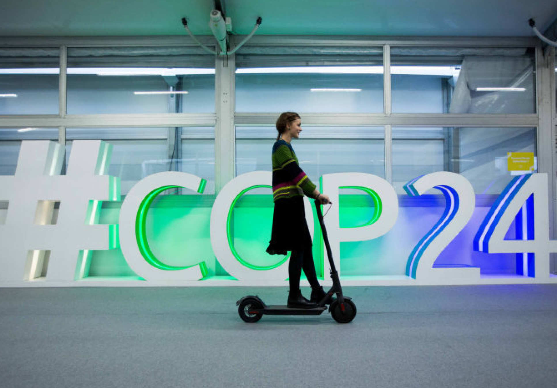 Person on a scooter going past the sign for COP24