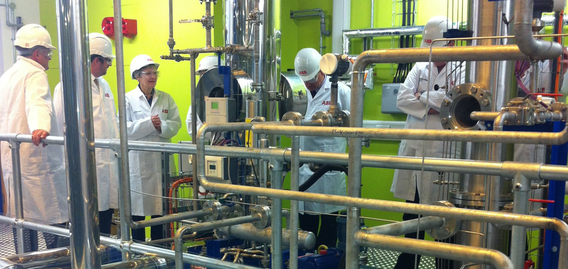 People wearing lab coats and hard hats inside the carbon capture pilot plant