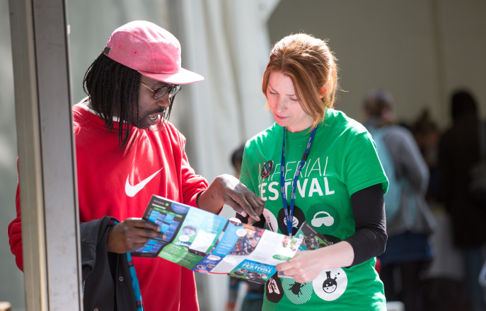 A volunteer helping a visitor reading a map