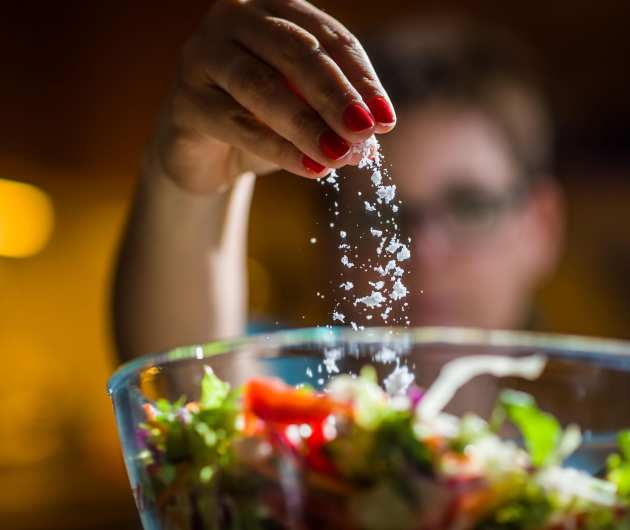 Woman putting salt in a salad