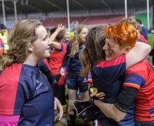 Two women rugby players embrace at Varsity