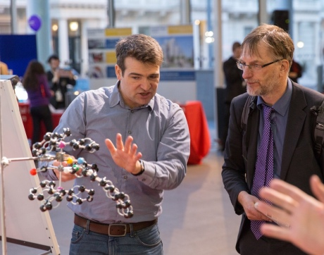 Researcher gesturing towards molecular model