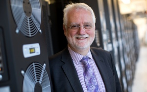 Professor Chris Hankin is standing next to a computer tower smiling