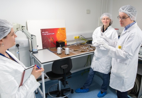Three people in white coats and hair nets in a lab with electrical equipment