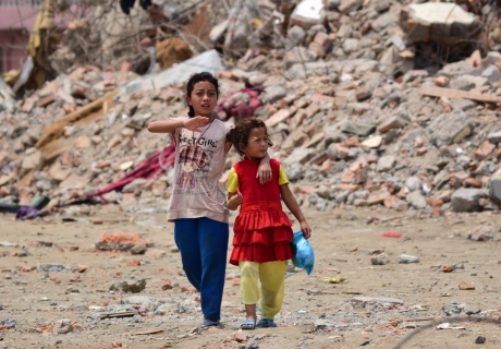 Nepal earthquake 2015 with children walking through the rubble