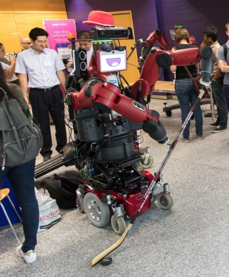 Robot DE NIRO, a large red robot, standing with a hockey stick