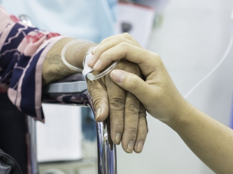 Close up of family member's hand on top of intensive care patient's hand in comforting manner
