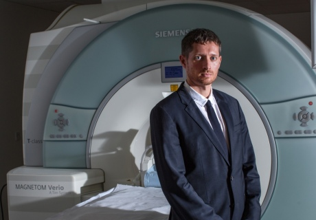 Dr Carhart-Harris stands by an MRI scanner