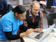 A student volunteer helps a resident with his laptop