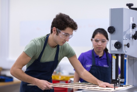 A student using a bandsaw to cut a sheet of thin wood, with a student mentor watching