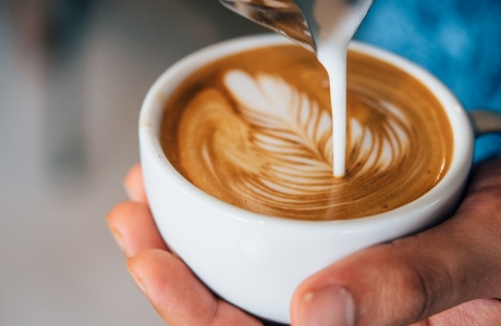 A strong latte being poured into a cup