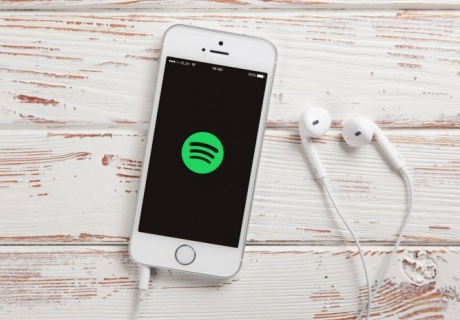An iPhone with headphones plugged in and the Spotify symbol on the screen.