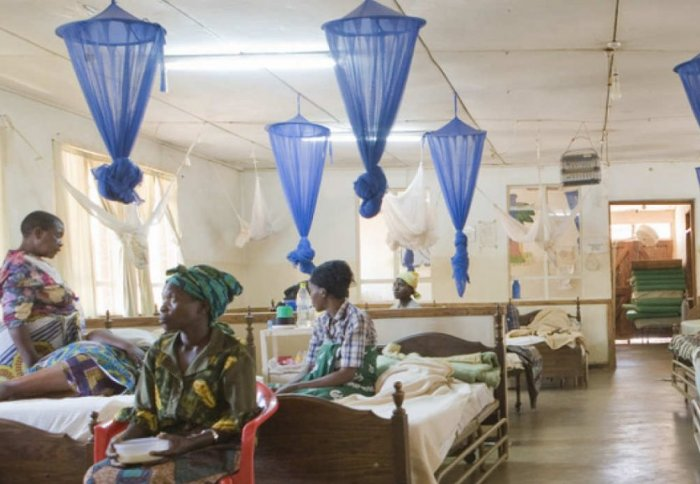 Mothers in a hospital with their children surrounded by bednets