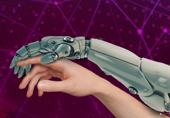 Robot arm against a human arm. Robot hand is holding a human finger in a protective stance.
