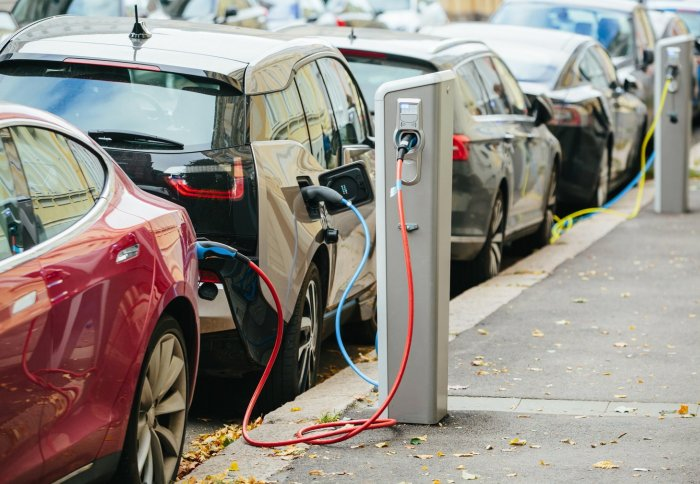 Electric Cars Plugged Into Charging Stations Along A Street