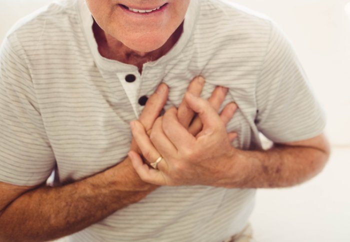 Image of an older man clutching his chest