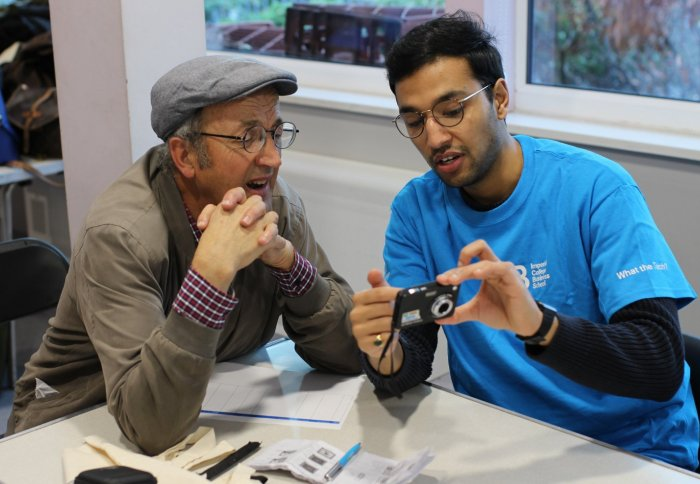 A student volunteer helps an elderly resident with a digital camera
