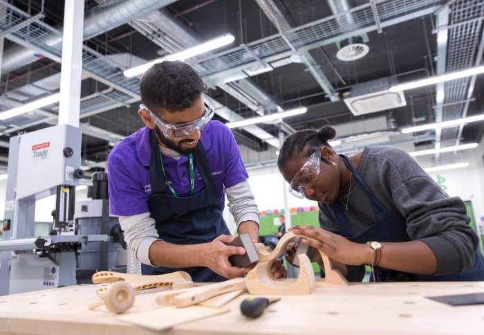 Two students wearing safety goggles sanding a wooden object in the workshop